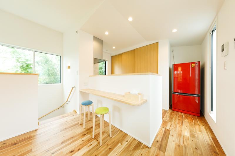 窓の外に緑が広がる目にも心地のいい2階のLDK。フローリングの無垢材の質感が相まったナチュラルテイスト。手元を立ち上げたキッチンはダイニング側にカウンターを造作しました。