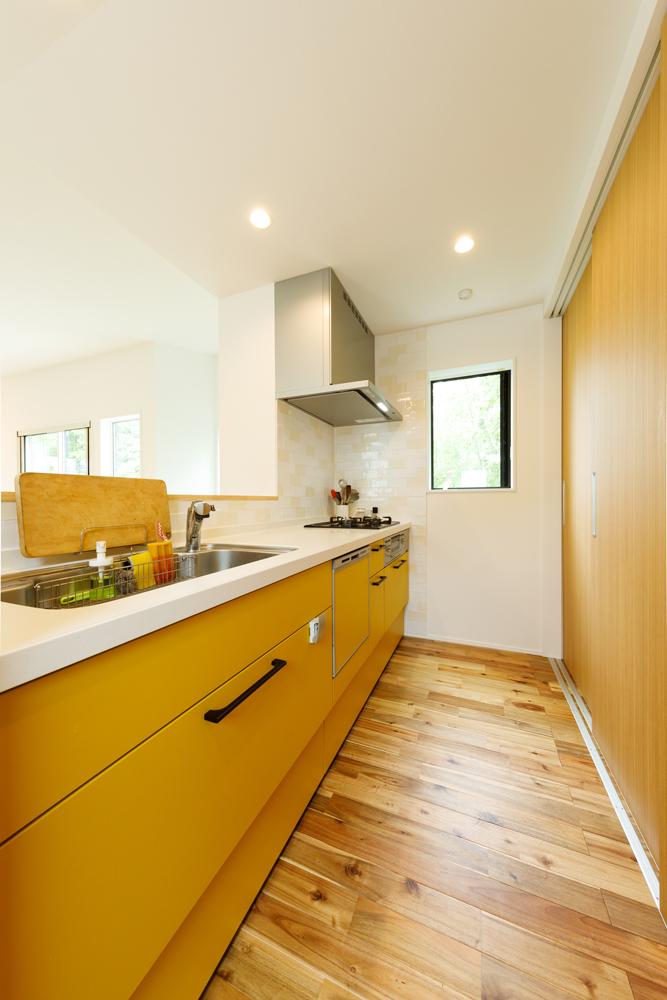 奥行きも幅も十分なキッチンは、素材だけでなく色合いもまとめてナチュラルな仕上がりに。壁のタイルは清潔感のある淡いトーンながらもリズムのあるモザイク柄にして楽しい空間に。