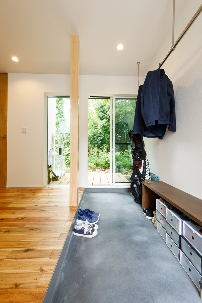 通り土間の玄関。テラスの向こうには近隣の緑が広がります。小上がりになったマルチスペースと一体化して、ライフスタイルに合わせて自由な使い方を楽しむ住まいです。
