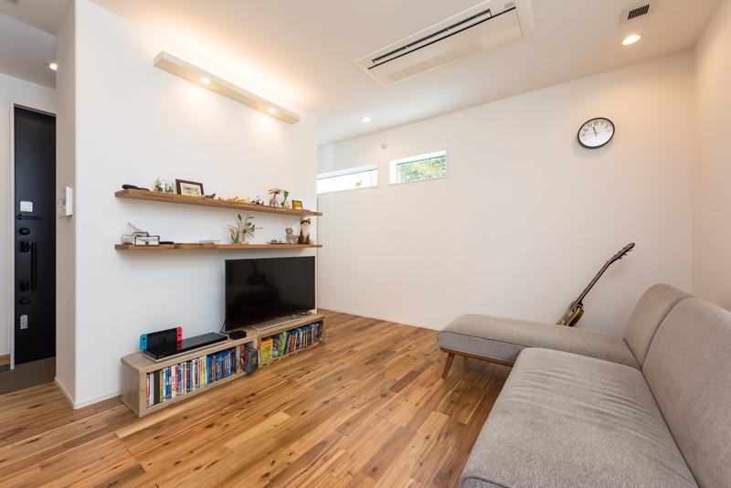 床にはアカシアの無垢フローリングを採用しました。テレビ背面の壁に設けた造作の棚は、リガードからの提案でフローリングと同じ素材を使い、空間に統一感を持たせています。街中の暮らしにあっては、プライバシーへの配慮も重要。玄関ドアを開けた時に、リビングが見えないように設計されています。