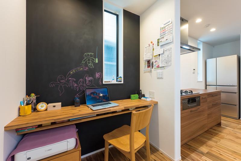 キッチン脇には、ご夫妻のワークスペースあるいは子どもたちのスタディスペースとして、マルチタスクに応えるカウンターを備えつけました。ご家族が互いに気遣いのできる絶妙な距離感に加えて、黒板壁を採用。家族みんなの共有スペースとして、楽しく機能性にもすぐれています。