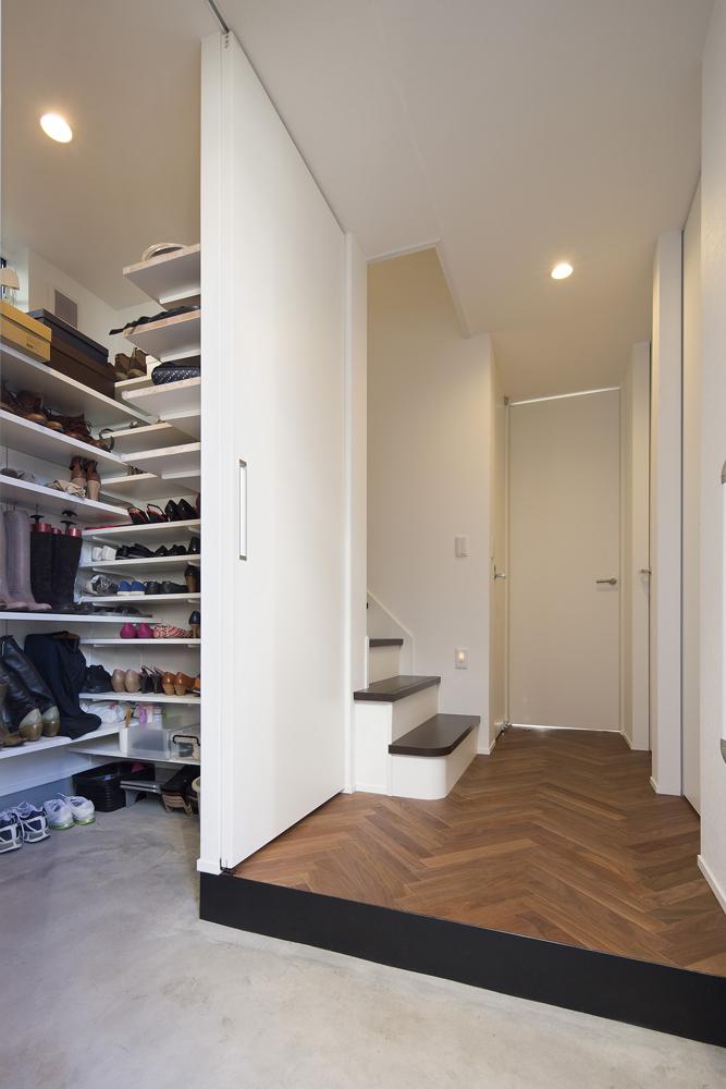 靴好きのAさまご夫妻。たくさんの靴が収納できるように、玄関には大容量のシューズインクロークを併設しました。来客時に玄関回りをすっきりと見せられるように、スライド扉で仕切ることができます。床はLDKと同様にヘリンボーン仕上げにこだわりました。