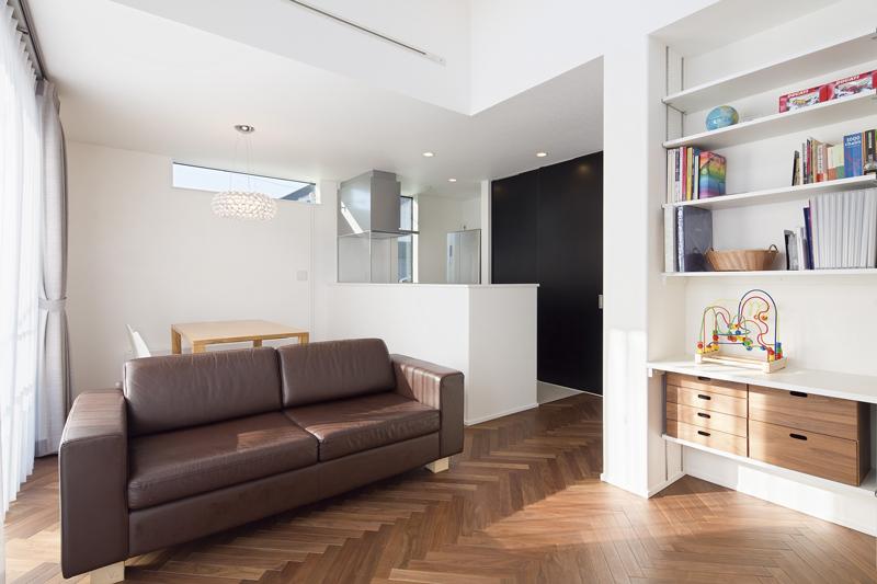高さにメリハリのある空間構成、漆喰の白壁とヘリンボーン床の質感のコントラストが鮮やかなLDK。キッチンの背面収納は黒のスライド扉を採用してアクセントにするとともに、空間全体に落ち着きを与えています。