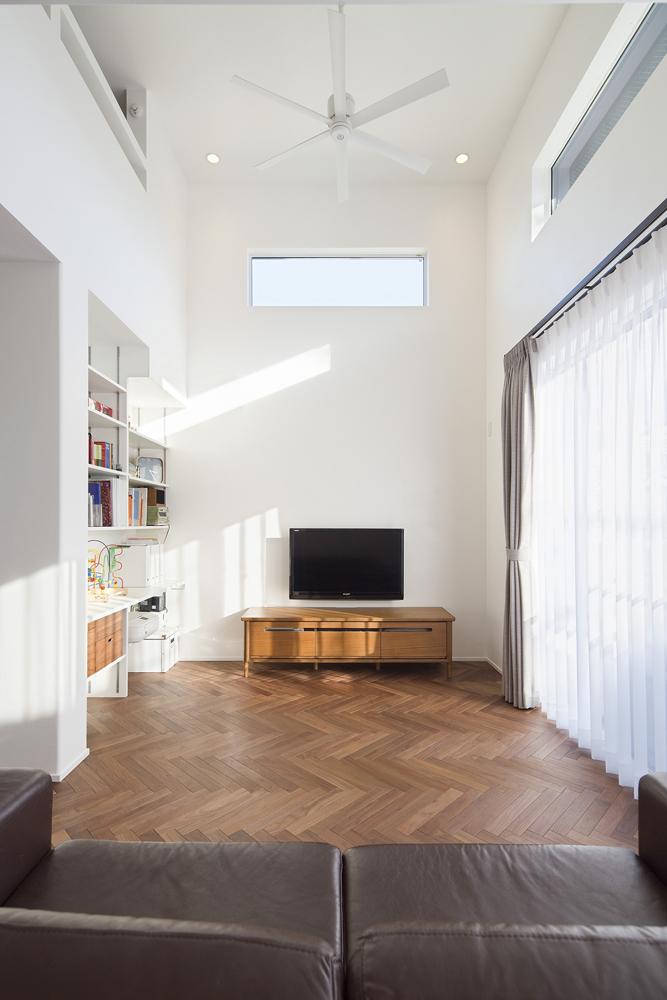 吹き抜けの開放感と相まって、伸び伸びとくつろいで過ごせる快適な空間設計。持ち込みのシーリングファンが白の漆喰壁と美しく馴染み、Aさまご夫妻のイメージ通りの空間を実現しました。