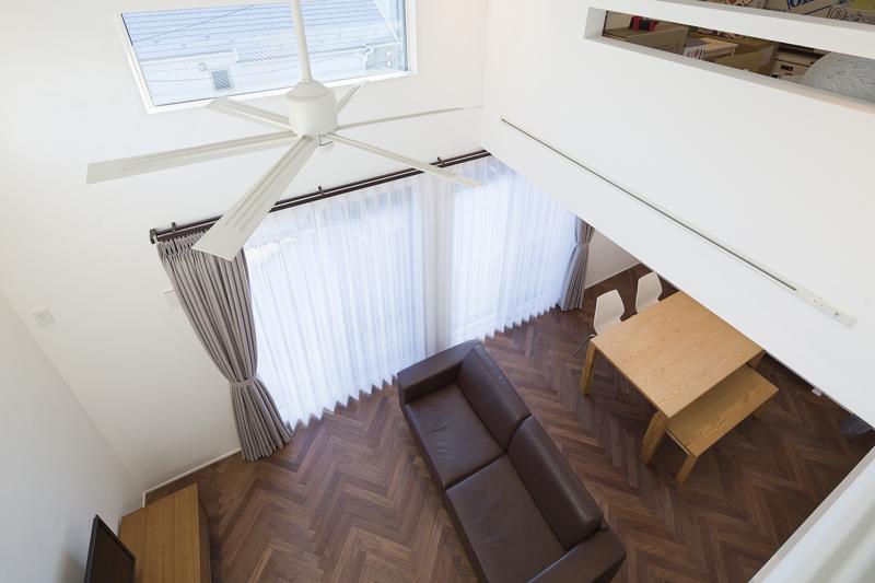 素材からこだわったのウォルナット無垢材のヘリンボーン床、Aさま支給のシーリングファンが空間デザインのアクセントになったLDK。吹き抜け高天井の心地いい陽だまりの下、憩いに満ちた暮らしをデザインしました。