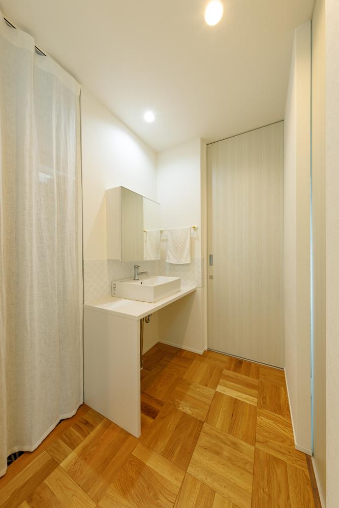 玄関ホールに隣り合うように洗面台をレイアウト。左手のカーテンの向こうはシューズクローゼットになっていて、子どもたちに帰宅してからのうがい手洗いを習慣にしやすいシンプルな動線です。