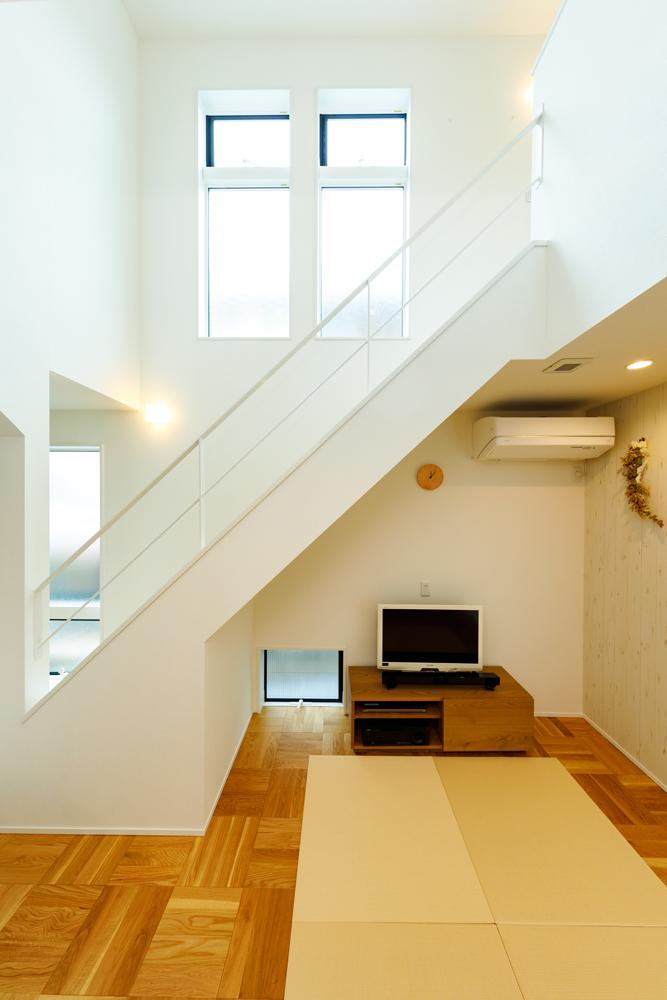 心地いい吹き抜けのリビング階段は、見上げると高天井の大空間に光が反射してまぶしく感じます。スケルトンの階段手すりは、高窓からの光が上下左右に広がるデザインです。