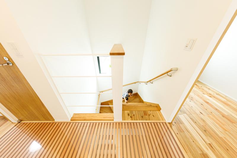 光と視線を通す2階のスケルトン廊下。住まい全体は立地に合わせたシンプルでコンパクトな構成ながら、空間の仕切りを極力なくし、縦横に空間をファジーにつなぐことで広がりのある開放的な住まいに仕上げられています。