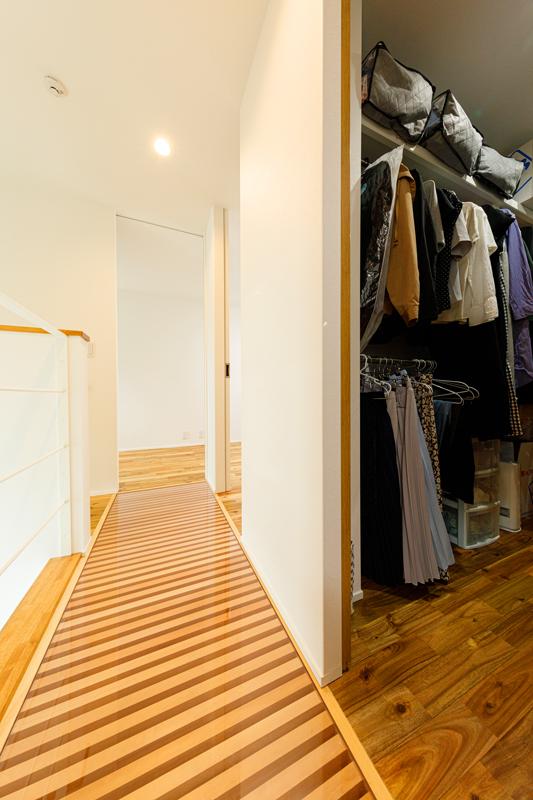 階段を上がると簀(すのこ)状のスケルトン廊下。視線や光の広がりにアクセントを与える仕掛け。2階の各居室のちょうど真ん中にはファミリークロゼットを配置。居室に収納スペースをつくらずに、居住スペースをそのぶん広く。