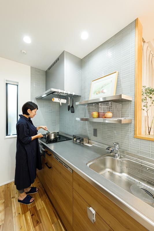 奥行きのあるキッチンは使いやすいことはもちろん、清涼感のあるタイルをあしらって落ち着きのある空間に仕上げています。カウンターは高く立ち上げて、リビング側から手元が見えないように。スリットの明かり窓もポイントです。