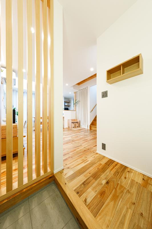 玄関とLDKはシームレスにつながる一体空間。壁を格子状にすることで玄関を明るく、さらに空間全体の開放感を損なわないように仕上げています。スイッチやコンセントにはインダストリアルなテイストのパーツをあしらい、こだわりを実現。