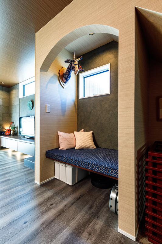 階段下のスペースを活用したニッチ空間。両サイドを壁に囲まれたスペースをアーチ型に切り取り、ベンチをしつらえています。背面クロスのトーンも変え、空間としての個性を強めることで、こもり感を演出しています。