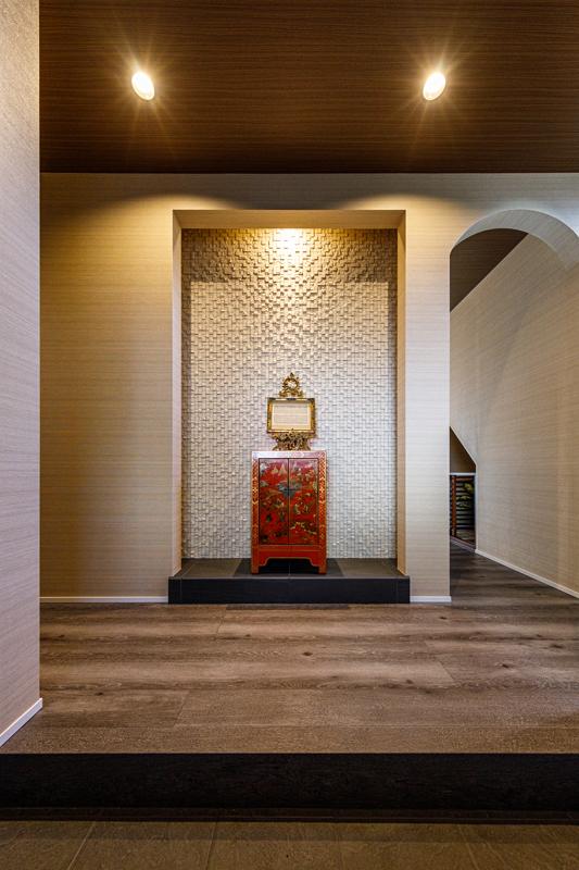 アジアンモダンなテイストでまとめられたシックな玄関ホール。玄関正面には白のモノトーンながら起伏のある立体的な幾何学模様のタイル壁。シンガポールのアンティークキャスターが据えられています。