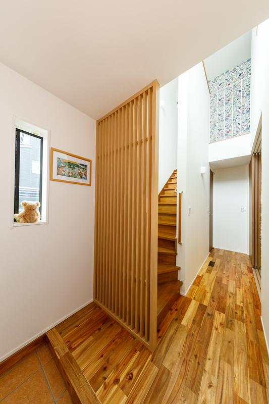 2階からの光で明るい玄関。壁ではなく格子にすることで光を通しながら、目隠しにもなり、圧迫感のない気持ちのいい空間の仕上がりに。1階の木目と2階の壁のクロスが互いに引き立て合っています。