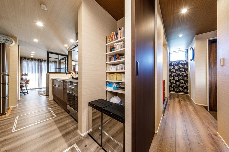 ダイニング側とは逆方向に玄関からつながる回遊動線。キッチン側の手前にはパントリー収納。「ここに収納できない分は買わないのが我が家のルール。必要以上に置くスペースを設けないことで、自分で片付ける習慣が身につきます」。