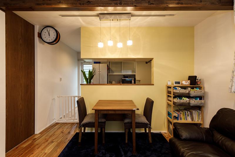 クリームイエローのかわいらしいキッチンカウンター。音符のように並んだペンダントライトや、駅舎風の掛け時計などこだわりのインテリアをアクセントに。梁を見せるなど木のぬくもりを感じる仕上がりに。