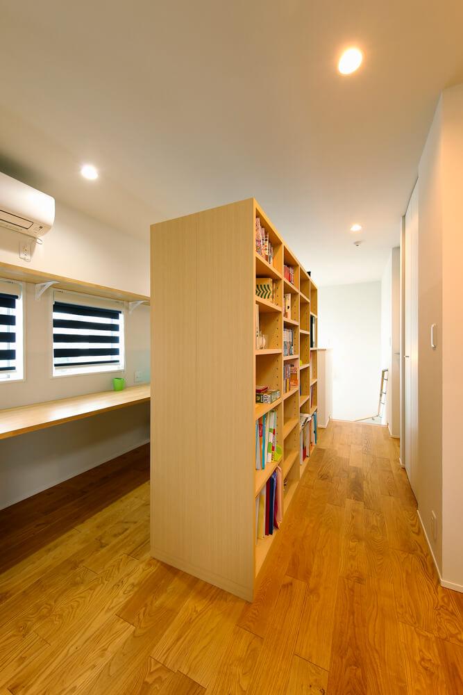"""2階のファミリーライブラリー。造り付けの本棚に背にしてスタディカウンターを設置。家族みんなが並んで読書をしたり、勉強したりできる、""""おうち図書館""""です。窓にはスリットのブラインドをつけました。"""