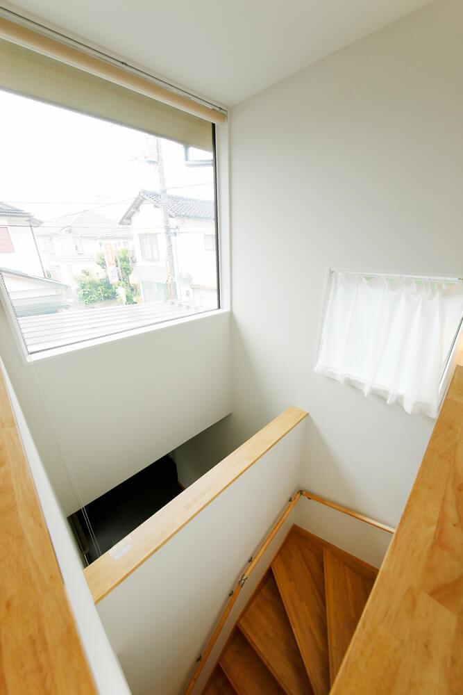 階段の吹き抜けにも大きく開いた窓を配置しました。2階に奥まで光を届けるだけでなく、玄関にも光をおとして住まい全体の採光性を高めながら、外観のアクセントにもなっています。