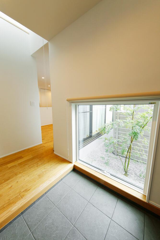 玄関には大きな地窓を設けました。窓の向こうに緑が映る風情のある仕上がりです。位置の低い開口部からの光は間接照明となって、ほどよい明るさで玄関にいっそうの落着きを持たせています。
