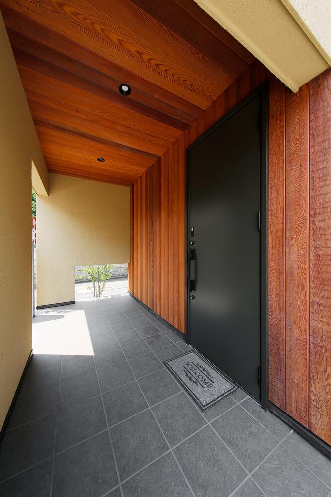 屋根のついた玄関ポーチは雨に濡れないだけでなく、玄関回りの風除けも担います。アイボリーの外壁に木の豊かな質感と玄関扉の重厚感が相まって風格のある仕上がり。植栽の緑が目に留まる風情豊かな空間です。