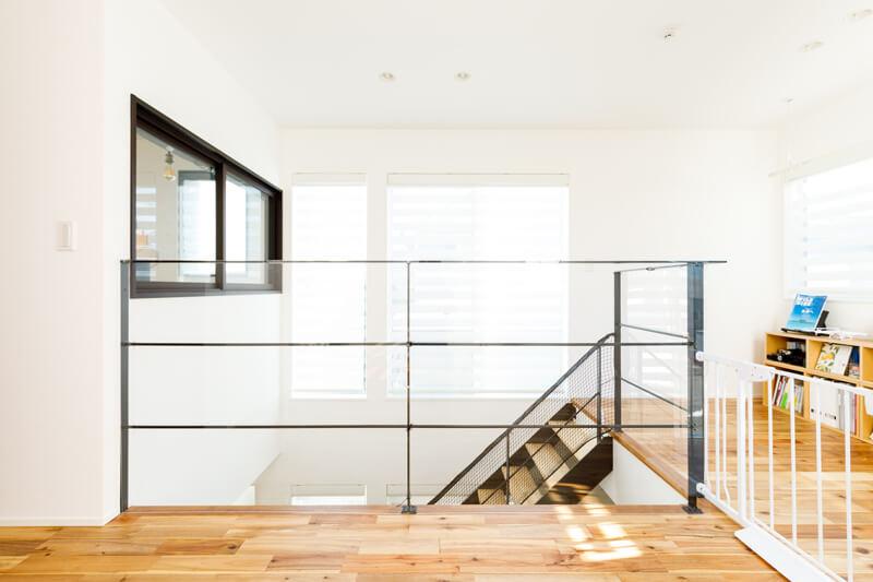吹き抜けの階段ホールには、スチールの骨組みにクリアパネルを組み合わせ、開放感を損なうことなく、安全性に配慮しています。右手は、ギャラリーも兼ねたライブラリーコーナー。