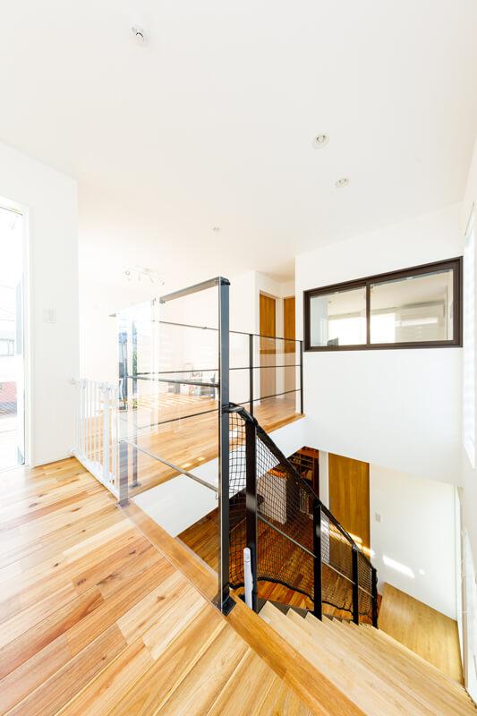 上下階をつなぐ開放的な吹き抜けの階段ホールは、室内物干しを備えたサンルームになっています。寝室と吹き抜けをつなぐ室内窓が光や風、声を伝えて、住まいの一体感をより深めています。