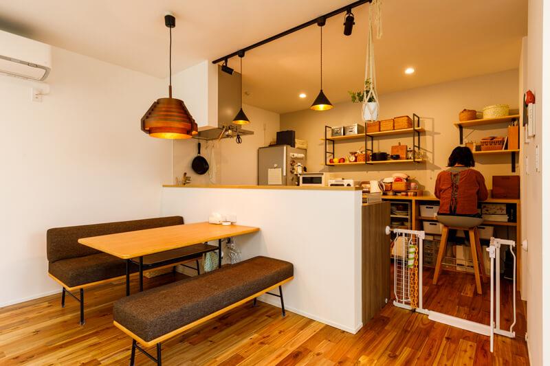 照明やダイニングセットなどのインテリアは無垢床の質感にもマッチするナチュラルモダンなテイストにまとめました。背面のキッチンカウンターの一角は、家事スペースや趣味の空間にもなるマルチユースなママコーナー。