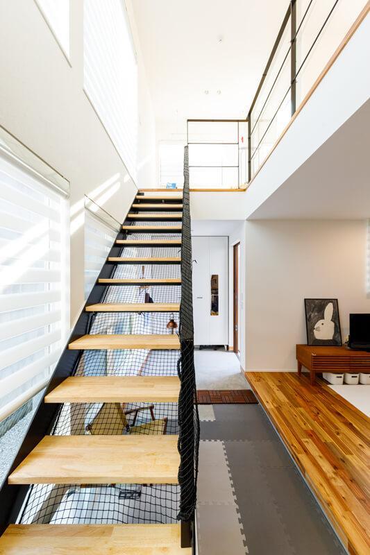 奥行きの深い土間玄関に、スケルトン階段の吹き抜けから爽やかな朝の光が差し込みます。土間玄関と縁側のような長い上がり框(かまち)は、住まいの内と外をつなぎながら曖昧に隔てる、居心地のいい中間領域です。