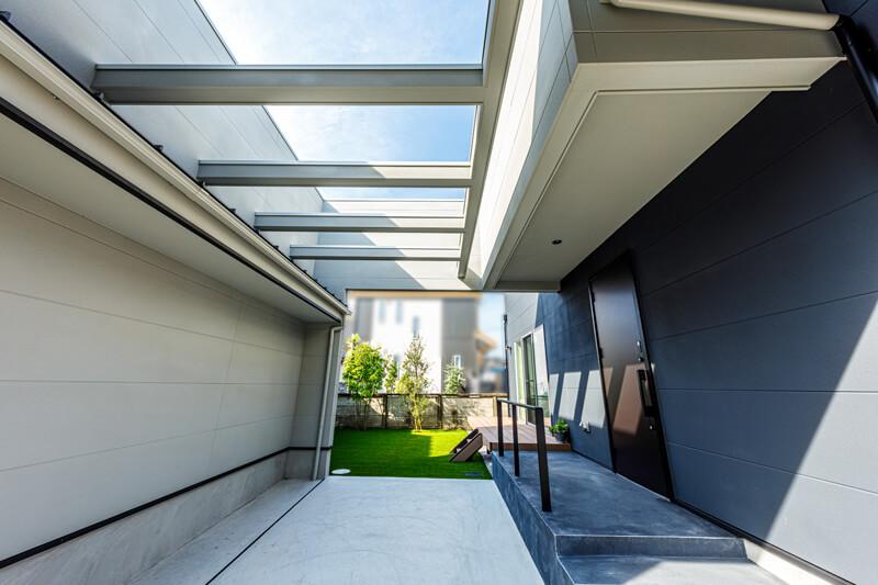 ゲートを潜ると玄関ポーチとガレージを挟んで、シンボルツリーが並ぶグリーンの鮮やかな内庭へとつながっていきます。手前に中間領域があることで、開放感を損なうことなく内庭のプライバシー性を保っています。