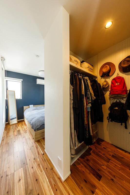 寝室のアクセントクロスは落ち着きのあるネイビーに。オープンなウォークインクローゼットは動線もシンプルで使いやすく、正面壁をパンチングボードにしてより機能性を高めています。