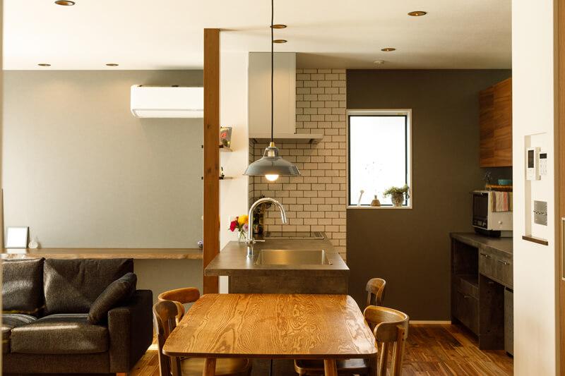 キッチンは、NYの地下鉄をイメージしたというホワイトタイルで壁をふかして立体的な仕上がりにしています。左手奥の壁に造り付けたカウンターは、ワークスペースやギャラリースペースにもなるマルチ空間です。