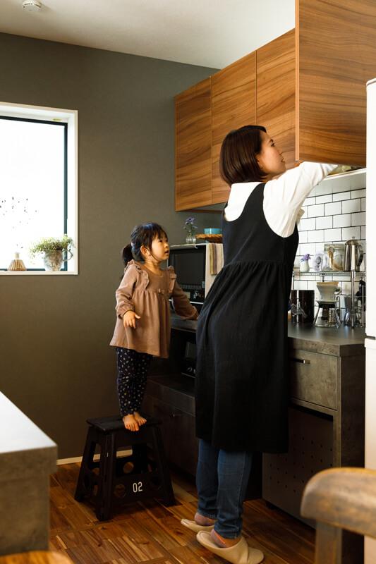 木扉の吊り戸棚を備えたバックセットは、ワークトップの奥行きが深いタイプ。コーヒー好きなご夫妻がコーヒーミルやドリッパーを並べ、淹れる時間を楽しんでいます。居心地のいいキッチンはそのまま、奥様のくつろぎ空間になりました。