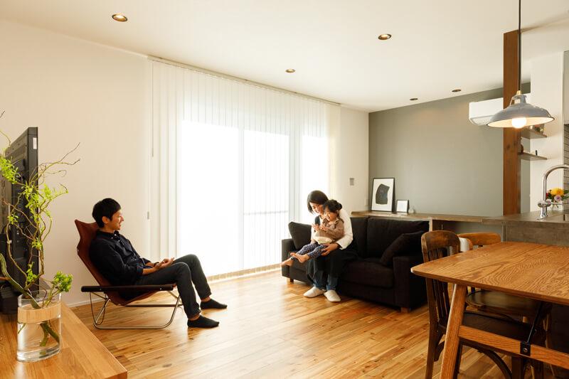 内庭のデッキにつながる大開口から、あたたかな光がLDKいっぱいに広がっていきます。白壁と無垢床に包まれた爽やかなナチュラルモダンの空間に、グレイッシュカラーのアクセントクロスが落ち着きを与えています。