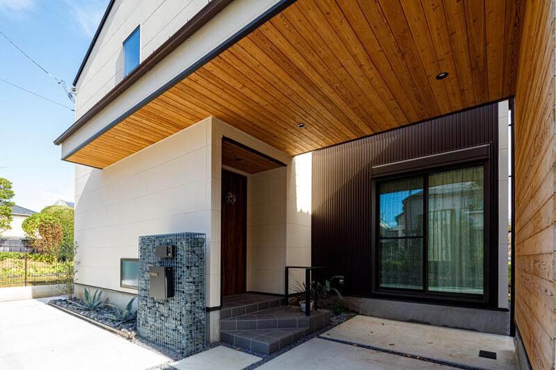 ガレージと一体化した玄関庇にも木材をあしらい、外観のアクセントに。国分寺モデルハウスでも採用されているガビオン門柱はご夫妻のこだわりの1品です。二世帯同居の場合の通院時などにまで配慮して、玄関を通らなくてもガレージからそのまま室内に入れるように居室を配置するなど、ユニバーサルデザインが施されています。