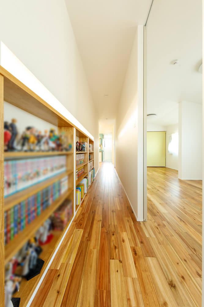 2階の廊下に棚を造作して、ディスプレイ&ライブラリースペースに。無垢床に座り込んで、家族が並んで書籍やマンガを読むなどしながら、のんびりと過ごせる家族だけの空間です。写真右手の居室は間に仕切り壁を入れてセパレートにすることもできます。暮らし方に寄り添う自由な空間を提案しています。