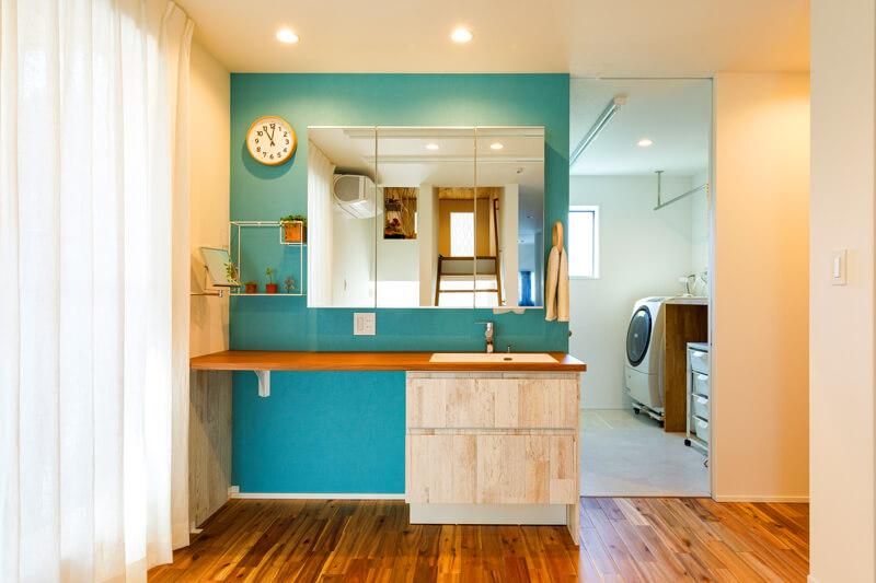 2階の家族の洗面台は爽やかなボタニカルテイストに。写真左手はバルコニーで、奥の水回りで洗濯したものを干すときの動線を短くしています。「これまでの住まいで暮らしていて『不便だな』と感じた部分をすべて解消しました」と奥様。