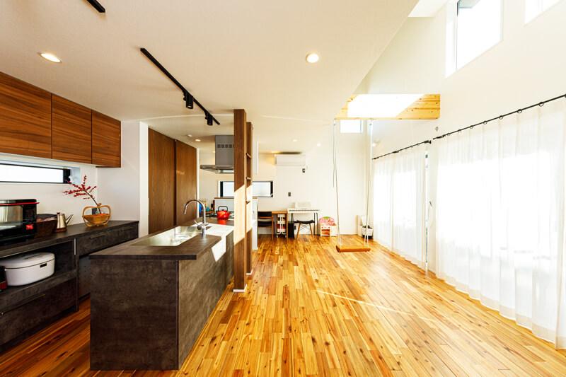木の質感が豊かなナチュラルテイストにモダンデザインを組み合わせたリビングキッチン。一面を占める大開口に加えて、吹き抜けの高窓からもやわらかな光が降りてきます。化粧梁から下がったブランコがリビングのキーデザイン。広々としたリビングは、ハンモックを取り付けることもできるように設計されています。