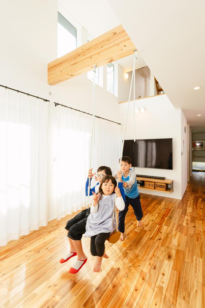 ナチュラルなシンプルモダンのリビング。上下左右の広がりに加えて、奥行きのある心地のいい空間をデザインしています。ブランコは子どもたちが一緒に乗ったり、大人が腰かけても安心の耐力設計。無垢床の心地よさに家では素足で過ごすことが多いようです。
