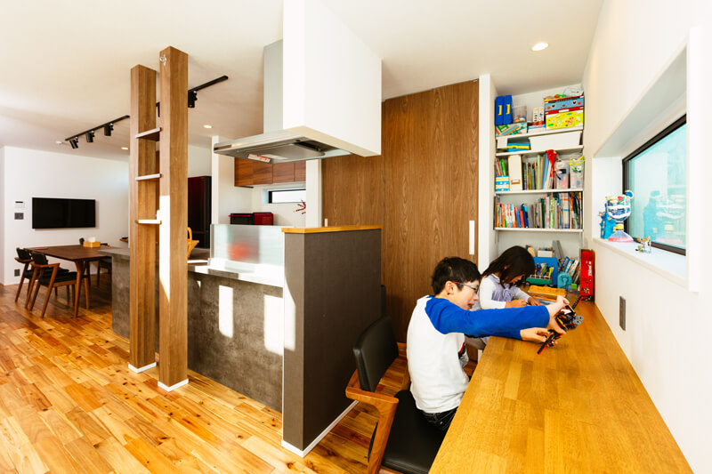 アイランドキッチンの脇に子どもたちのスタディカウンターを造り付けました。「料理や片付けをしながらでも、宿題をみてあげられます。親が近くにいることで子どもたちも安心するようです」と奥様。子どもたちが仲良く並んで、勉強やお絵かき、プラモデル作りなど思い思いに過ごしています。