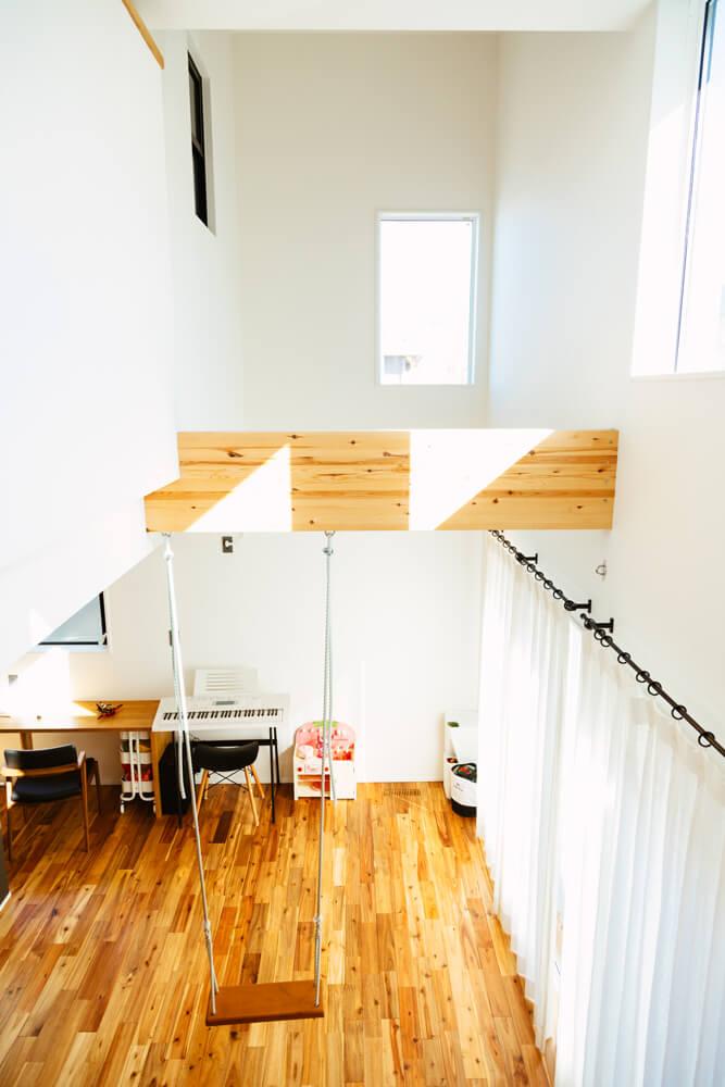 階段の踊り場からリビングを覗き込むことができます。吹き抜けから家じゅうに光が広がっていきます。開放的な空間設計に加えて、いつも家族がつながりを感じられる暮らしをデザインしています。