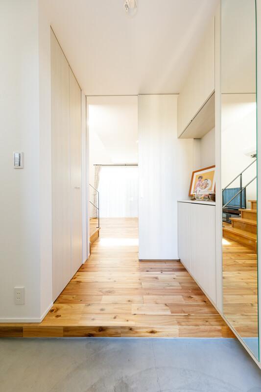 玄関扉を開くと一斉に光があふれ、LDKの奥に向かって視界が広がっていきます。壁や天井、建具の白が眩しいナチュラルモダンテイストでまとめられています。トールタイプの姿見鏡を造り付けました。