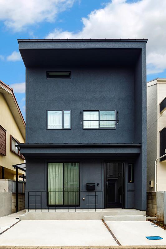 街並みに際立つモダンデザインの外観。ロフトスペースの分、2階の天井が高くなっています。玄関扉は防犯複層式の艶やかな全面ガラス仕上げ、外壁は色の深いネイビーのスタッコ仕上げ、アクセントにモールを入れています。