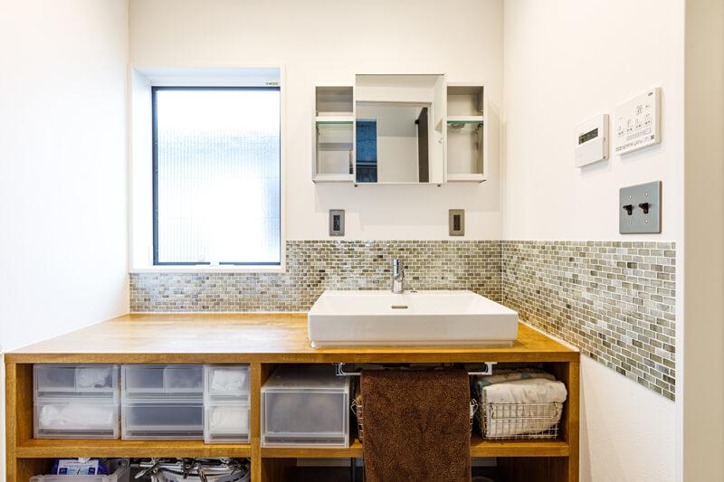 目の細かいモザイクタイルをあしらった洗面室。洗面ボウル横に広いカウンタースペースがあるので、化粧や身支度にも便利。収納は扉をつけずにオープンにしておくことで、すっきりときれいに見せることを意識しています。