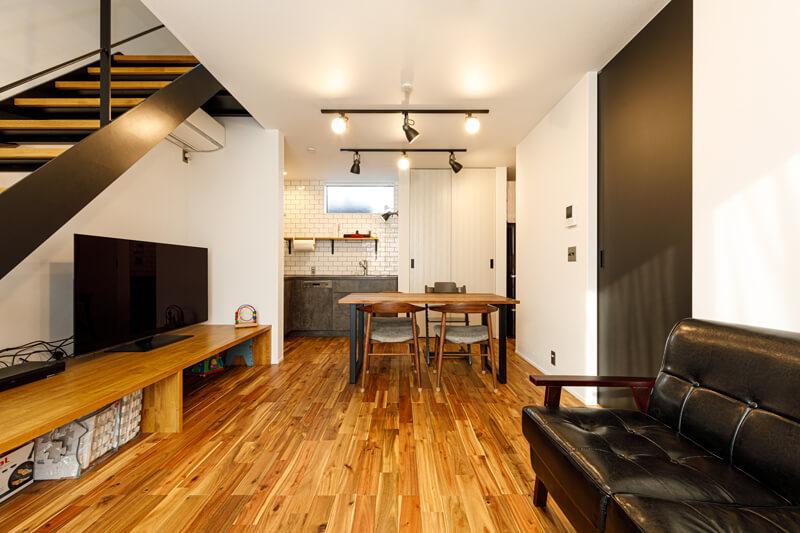 ご家族が憩いの時間を過ごす、ワンフロアのLDK。階段下にはTVボードを兼ねたカウンター収納を設置しました。ライティングレールにスポットライトを並べて、スタジオのような雰囲気のある空間に仕上げました。