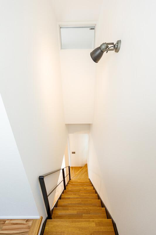 清々しい白壁が美しい吹き抜けのリビング階段。壁や天井に反射して家じゅうに光が広がっていきます。仕切りの少ないオープンな空間設計は、高気密・高断熱のすぐれた住宅性能ならでは。
