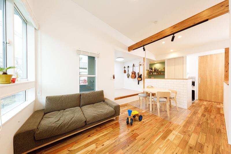 無垢材の質感豊かなナチュラルテイスト。天井が高く、窓のフォルムにまでこだわったヨーロピアンなコテージスタイルのLDK。キッチンの奥には、ペールグリーンのアクセントクロスをあしらったバーカウンターを造り付けました。