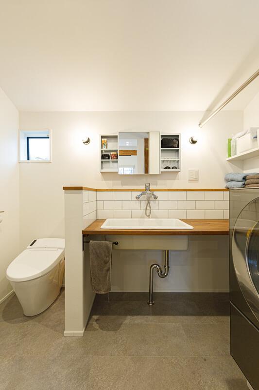 機能性あふれるブルックリンスタイルの洗面室。洗面台の下を収納スペースにせず空けることで、空間全体をすっきりシンプルで軽やかな印象に仕上げています。鏡台左右の照明は裸電球にするなどディテールにこだわっています。