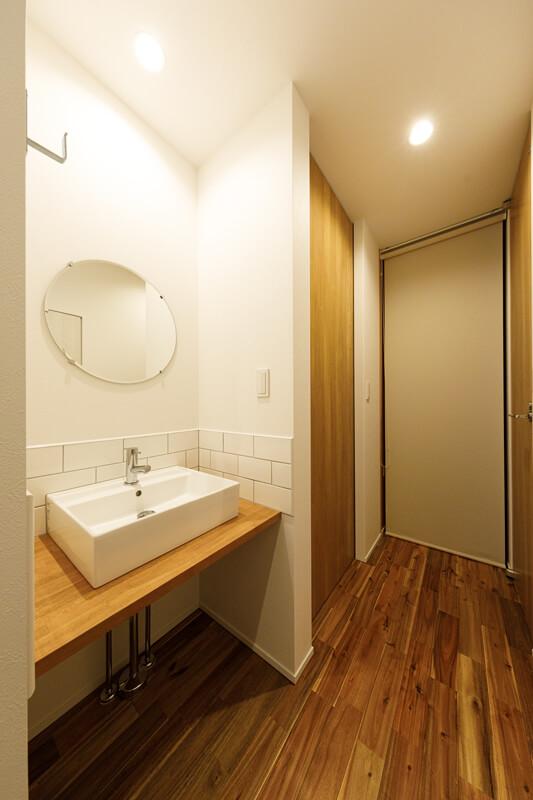 玄関脇には洗面台を設置しています。動線上にあるので、お出かけの身支度や帰宅時のうがい・手洗いにも便利。正面はウォークインクローゼット。日々の使いやすさを考慮して、仕切りにはロールスクリーンを採用しました。