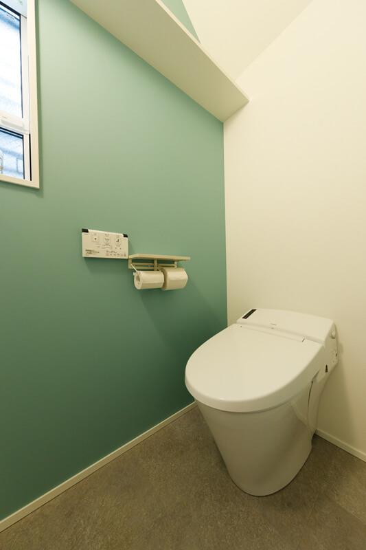 トイレの壁には爽やかでありながら落ち着きのある若竹色のアクセントクロスをあしらいました。明かり採りと換気通風を兼ねた小窓も空間のアクセントになっています。