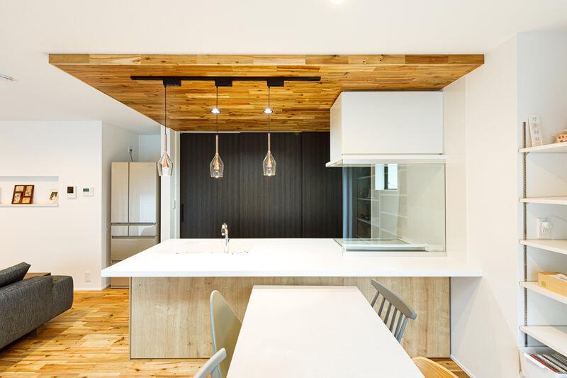 白が映えるモダンスタイルのキッチン。背面収納の扉を黒にして引き締め、天井に木をあしらうことで存在感を際立たせています。天板の高さを低くして圧迫感をなくして、すっきりと見せながら、ダイニング側からも使いやすくしています。